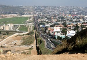 An image of the US-Mexican border. A corrugated iron fence separates Tijuana on the right from San Diego on the left.