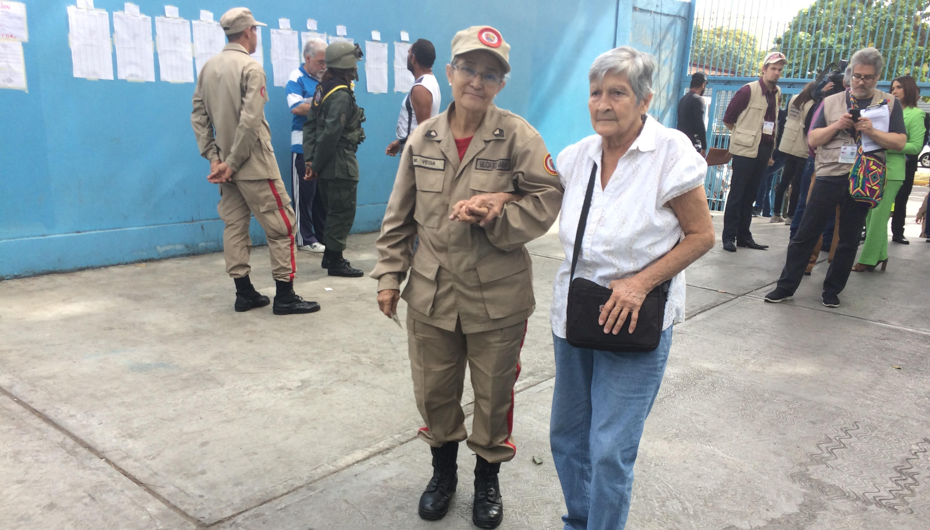 An elderly Venezuelan woman is accompanied to the polling centre